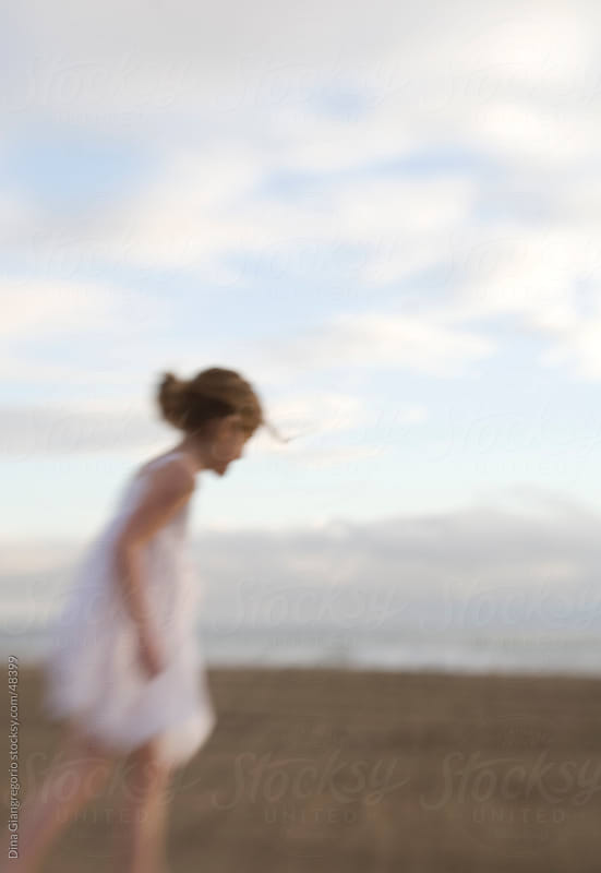 Side view of Girl in white dress walking across beach with hair pulled back by Dina Giangregorio for Stocksy United