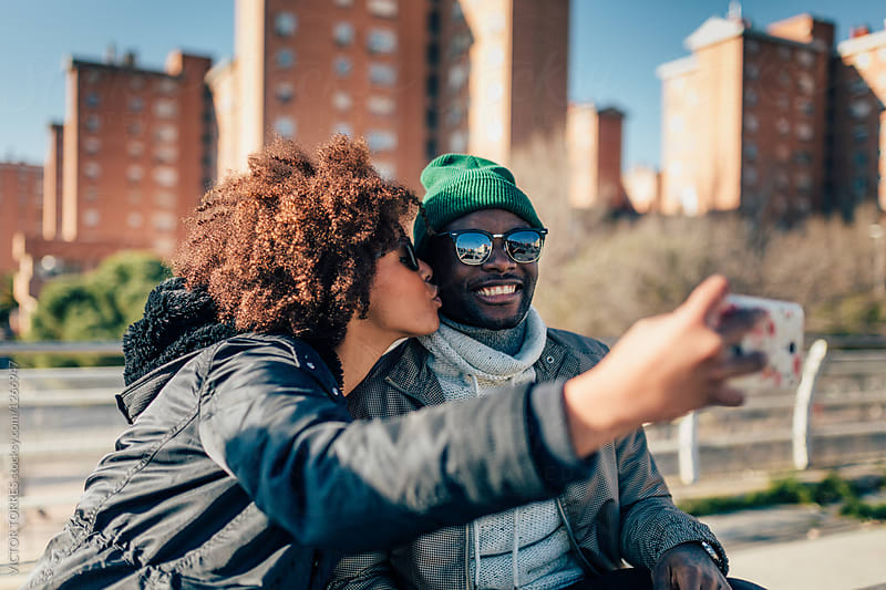 Afro american woman kissing her boyfriend while taking a selfie  by VICTOR TORRES for Stocksy United