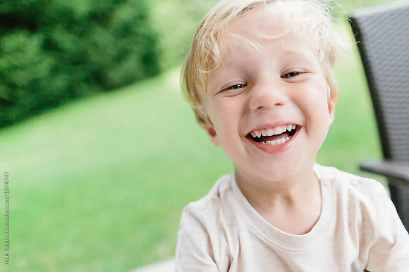 Cute little boy laughing in yard by Amir Kaljikovic for Stocksy United