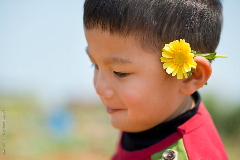 Little boy smiling with a flower by Lawren Lu for Stocksy United