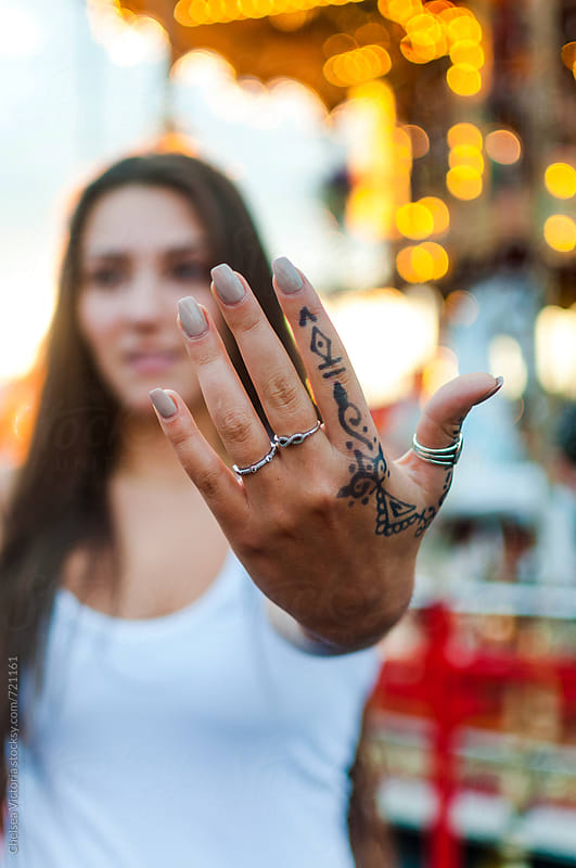 A women at a carnival with henna on her hand by Chelsea Victoria for Stocksy United