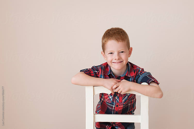 Portrait of an adorable redhead boy smiling, against a beige background kneeling on a white chair. by Lea Csontos for Stocksy United