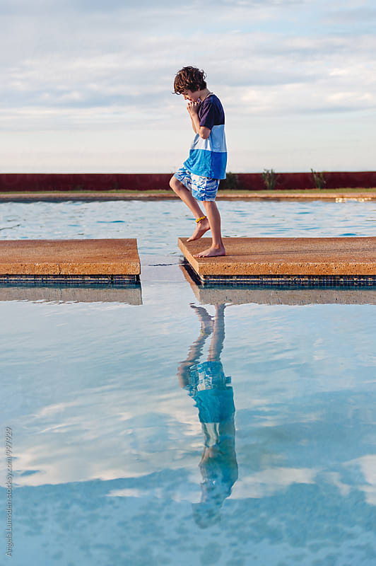 Boy reflected in a swimming pool by Angela Lumsden for Stocksy United