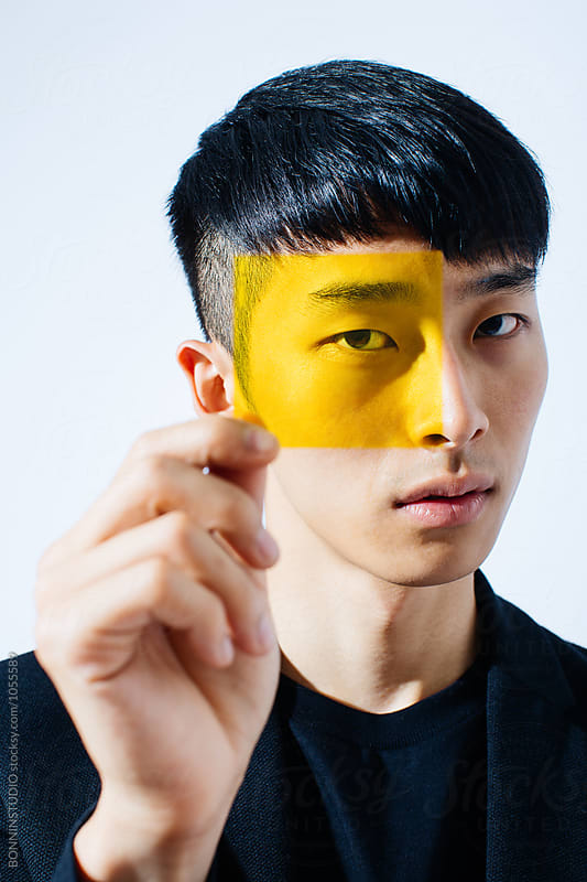 Portrait of an asian man looking through yellow glass. by BONNINSTUDIO for Stocksy United