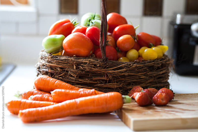 A basket of fresh tomatoes and carrots rest on kitchen counter. by Cherish Bryck for Stocksy United