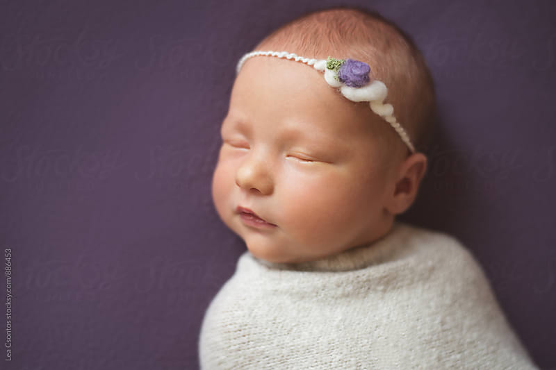 Beautiful newborn baby girl sleeping on a purple blanket. by Lea Csontos for Stocksy United