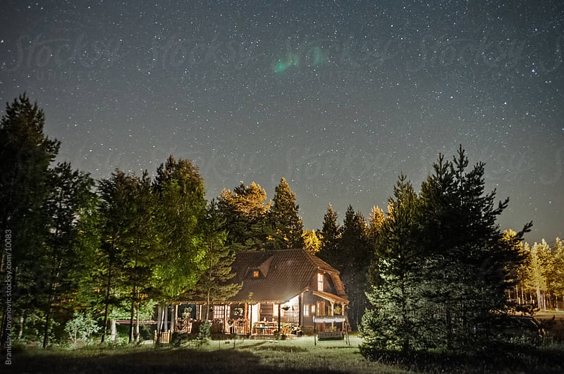 Mountain house in the woods with a starry sky by Branislav Jovanović for Stocksy United