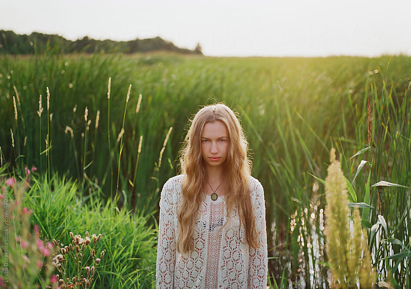Young woman standing in the field of green grass in sunlight by Lyuba Burakova for Stocksy United