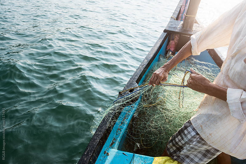 fisherman pulling his net out of the water  by RG&B Images for Stocksy United