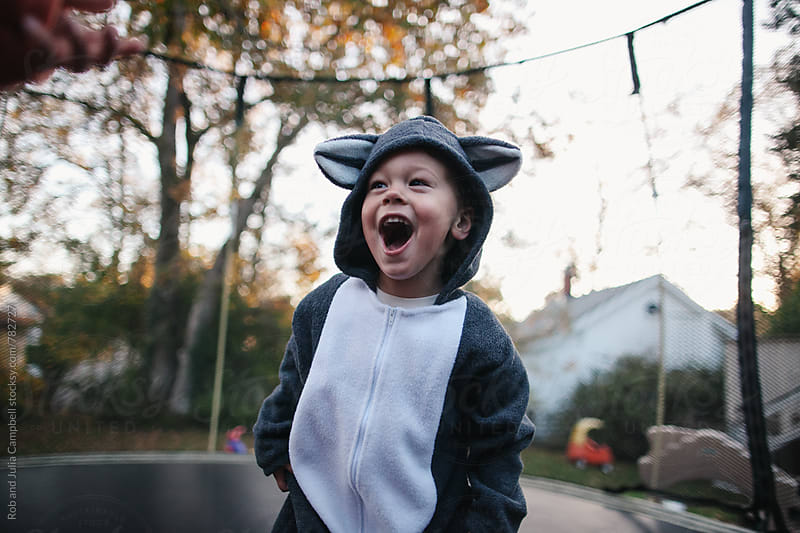 Cute boy in raccoon costume jumping on trampoline by Rob and Julia Campbell for Stocksy United