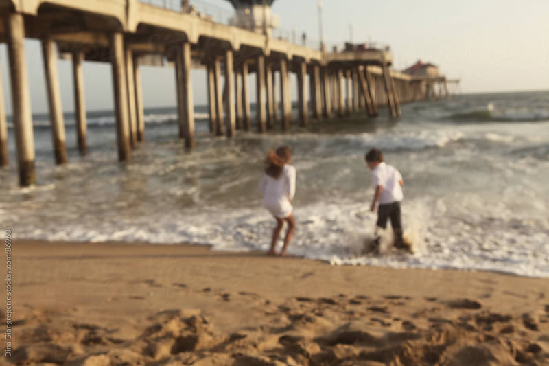 Two children playing on beach by Dina Giangregorio for Stocksy United