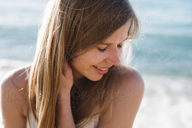 Happy and smiling woman portrait at the beach by Simone Becchetti for Stocksy United