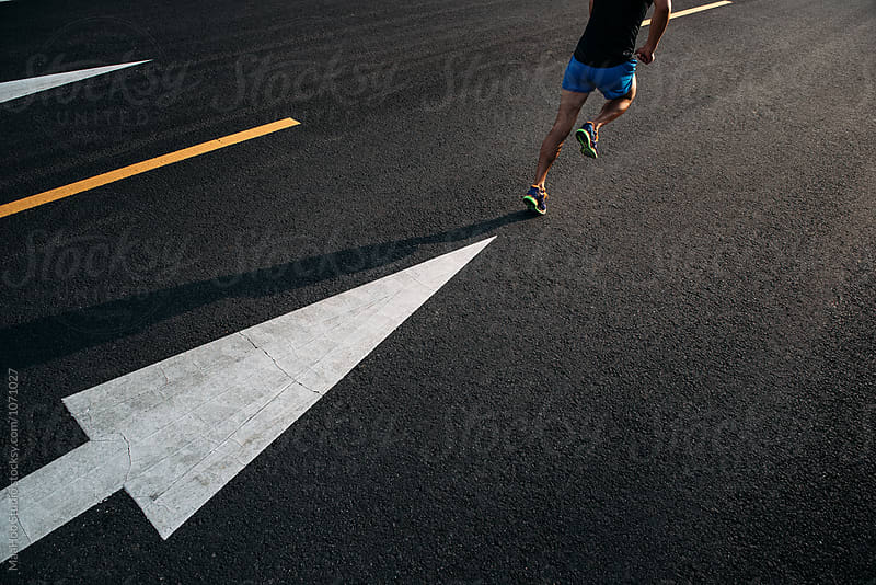 Young man running on road with arrows by Maa Hoo for Stocksy United
