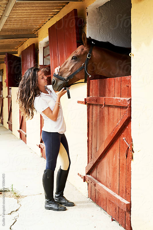 smiling brunette jockey stroking horse's nose by Guille Faingold for Stocksy United