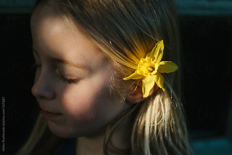 A little girl with her face in the sun and a daffodil in her hair. by Helen Rushbrook for Stocksy United