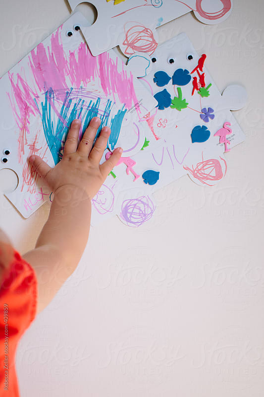 close-up of a child's hand touching her artwork on the wall by Rebecca Zeller for Stocksy United