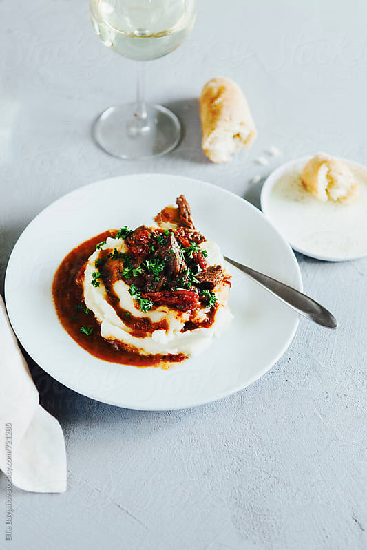 Sun-dried tomato beef stew over mashed potatoes by Ellie Baygulov for Stocksy United