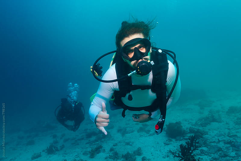 Scuba diver showing hang loose sign underwater  by Jovana Milanko for Stocksy United