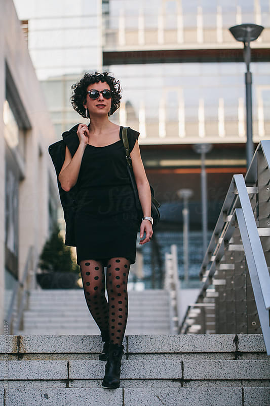 Young woman walking in the business district by Davide Illini for Stocksy United