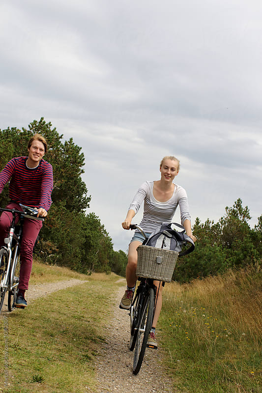 Young couple cycling through nature by Marcel for Stocksy United