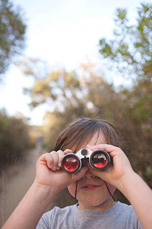 A young boy looking through binoculars by Natalie JEFFCOTT for Stocksy United