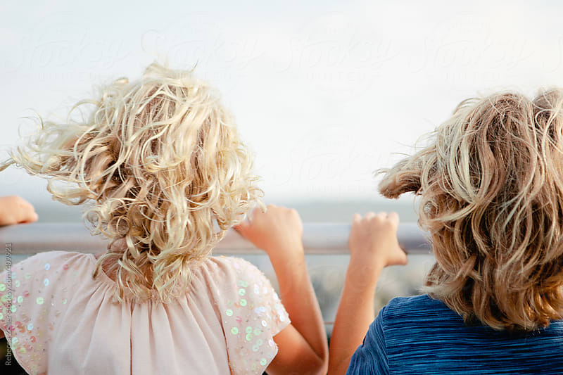 two kids hold on to the railing of a ferry while the wind whips through their hair by Rebecca Zeller for Stocksy United