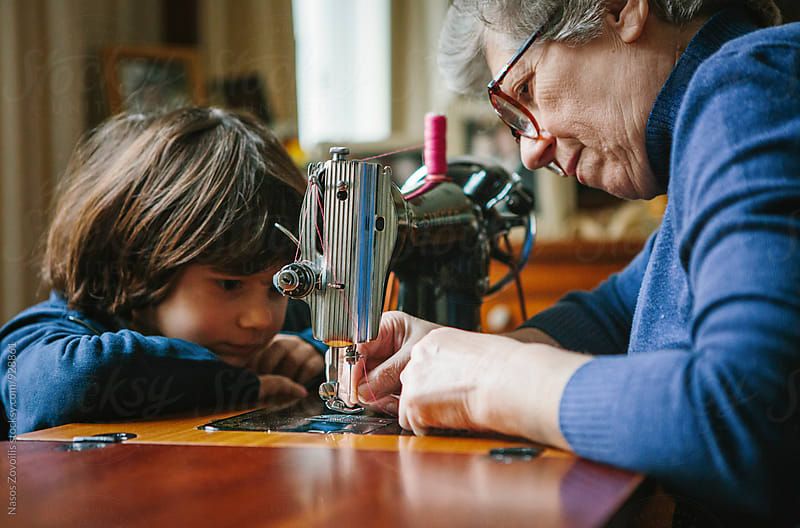 Grandson watching his grandmother working on a sewing machine by Nasos Zovoilis for Stocksy United