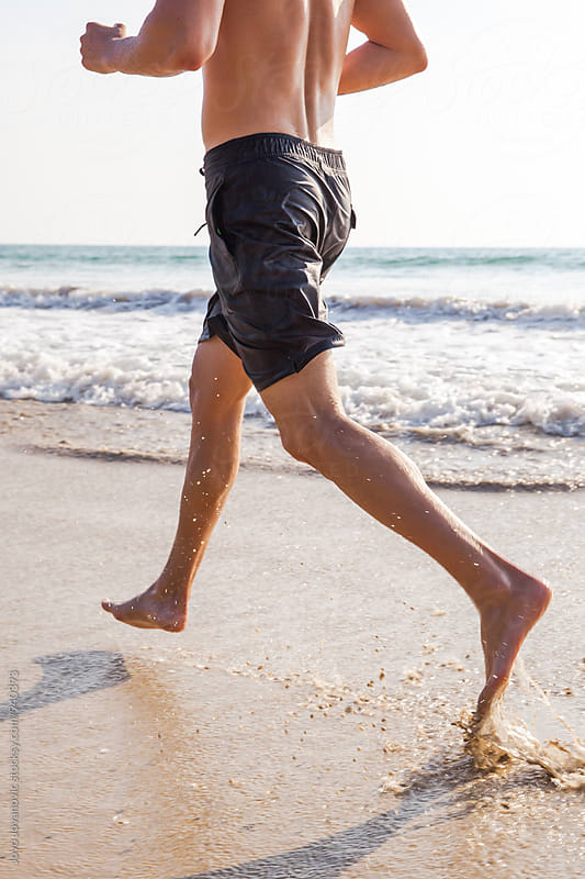 Man running on the beach at sunset by Jovo Jovanovic for Stocksy United