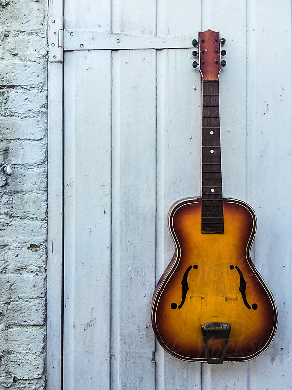 Vintage guitar hanging against a wall with copyspace by kkgas for Stocksy United