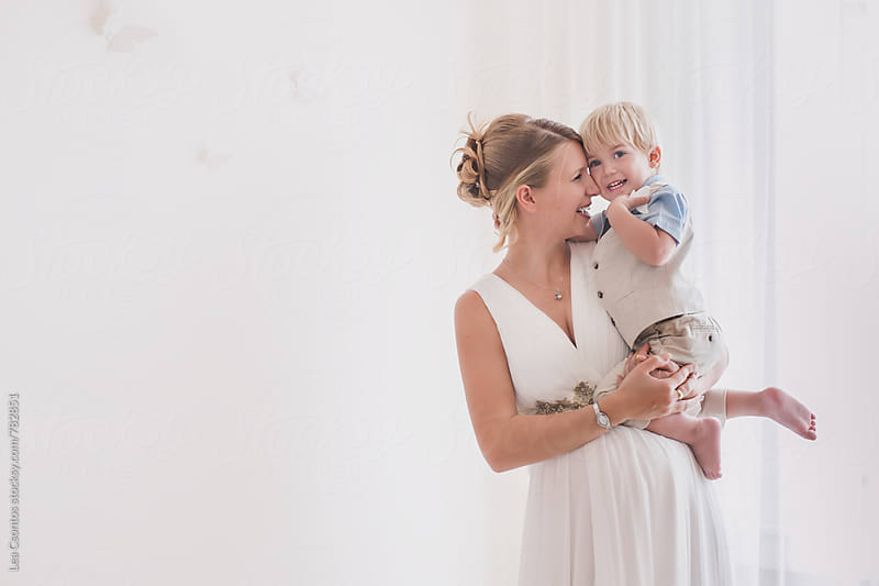 Beautiful pregnant mother holding her cute son in her arms by Lea Csontos for Stocksy United