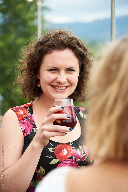 elegant smiling woman with curly hair drinking at party by Guille Faingold for Stocksy United