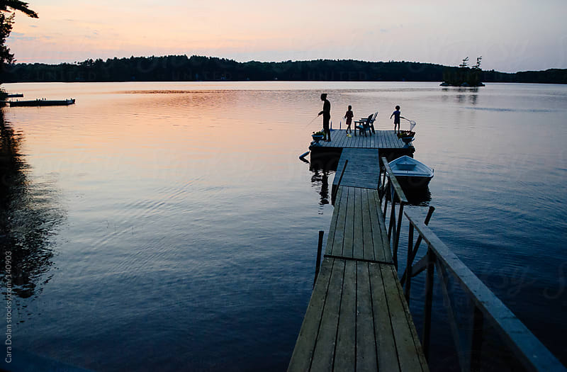 Family enjoys the lake at sunset by Cara Dolan for Stocksy United