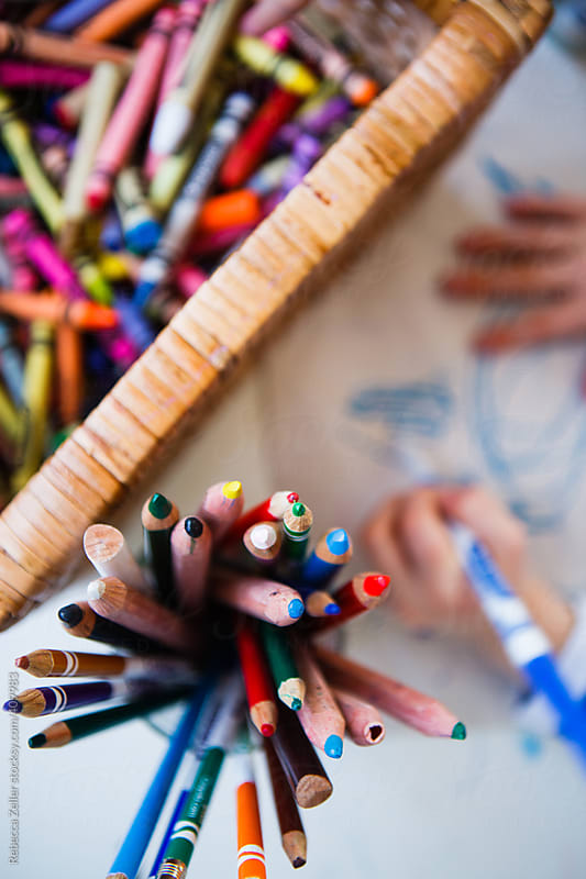 toddler hands coloring with markers, colored pencils, and crayons by Rebecca Zeller for Stocksy United