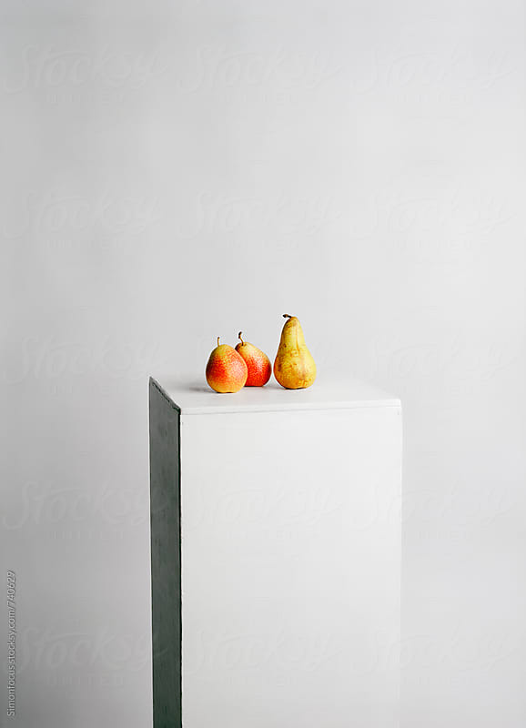 Three organic pears on pedestal by Simon DesRochers for Stocksy United