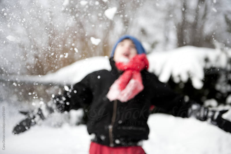 Boy joyously throws snow into the air by Cara Dolan for Stocksy United