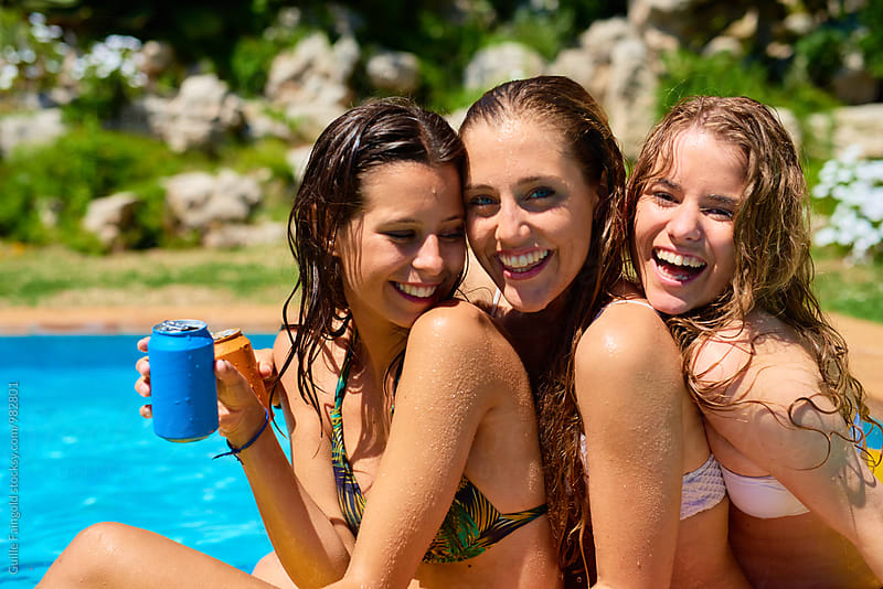 Three cheerful girls with wet hair laughing on air matress in pool by Guille Faingold for Stocksy United