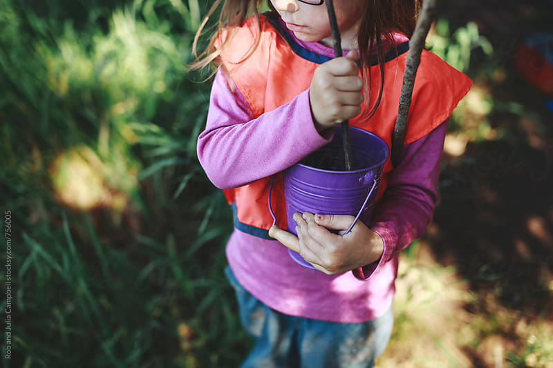 Cute girl stiring bucket with sticks in nature by Rob and Julia Campbell for Stocksy United
