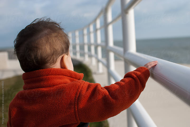 young boy stands at railing near lake by Margaret Vincent for Stocksy United