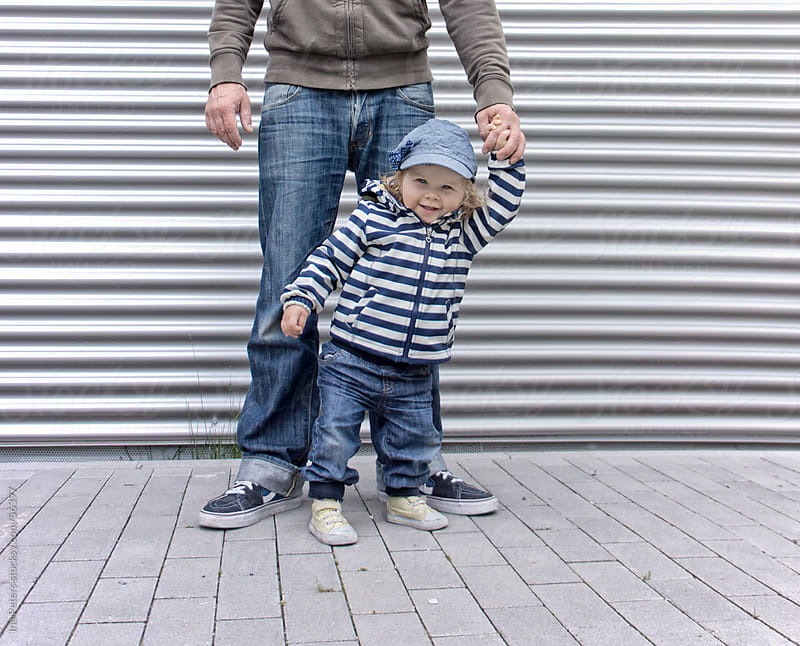 People: Toddler smiling while holding fathers hand by Ina Peters for Stocksy United