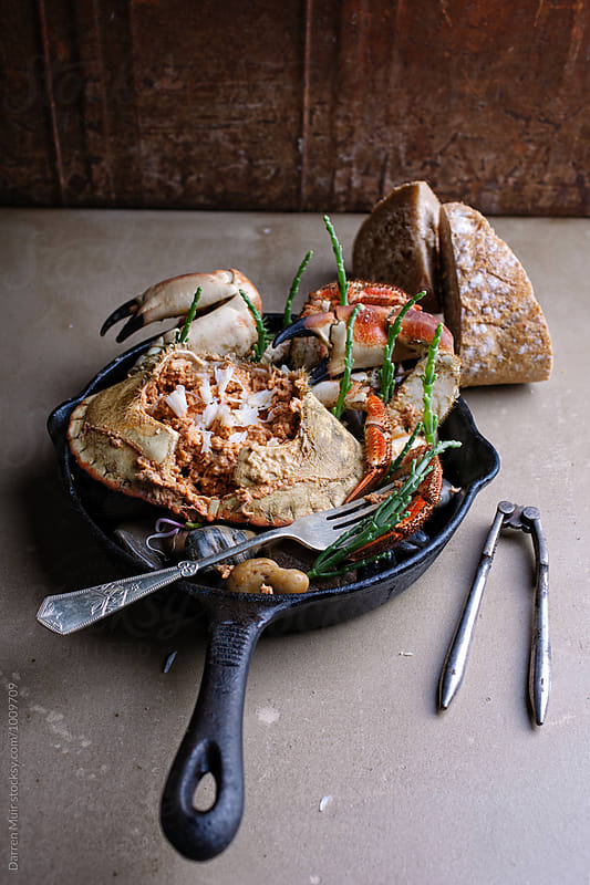Dressed crab appetizer in a skillet. by Darren Muir for Stocksy United