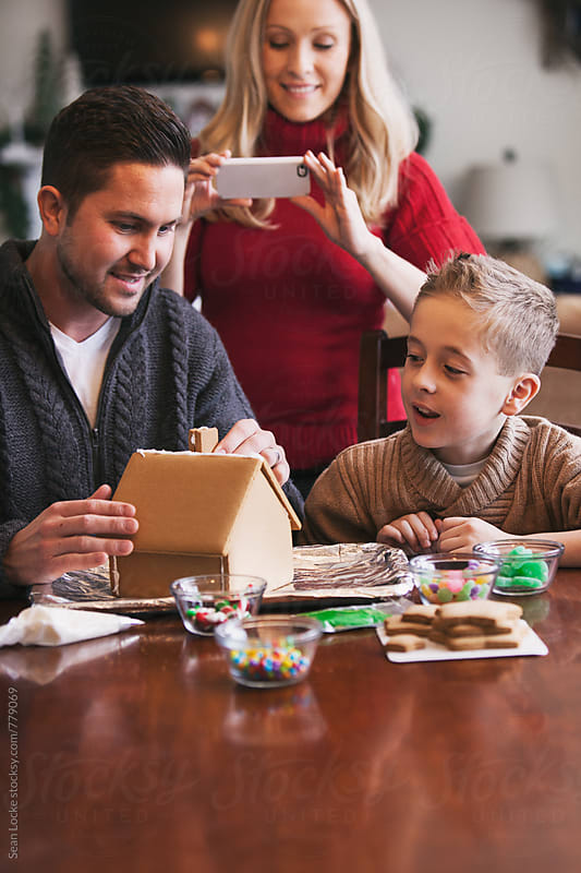 Christmas: Mother Takes Photo While Decorating Gingerbread by Sean Locke for Stocksy United