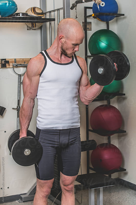 man lifting weights at the gym by Andreas Gradin for Stocksy United