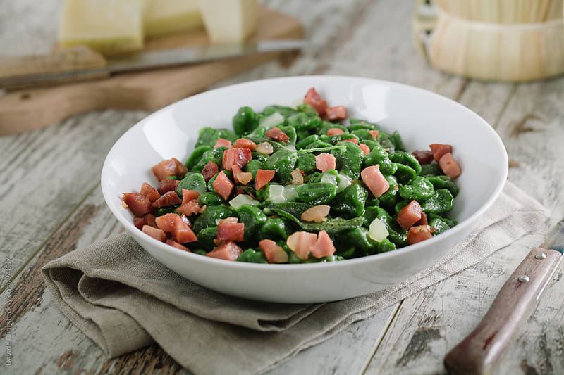 Green gnocchi with cheese and smoked ham by Davide Illini for Stocksy United