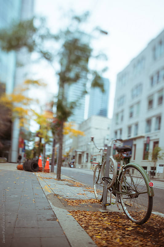 bicycle parked on a street in Toronto by Javier Pardina for Stocksy United