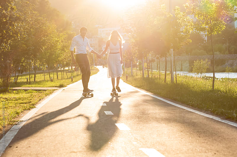 Active couple having fun riding skateboards on a urban trail  by RG&B Images for Stocksy United