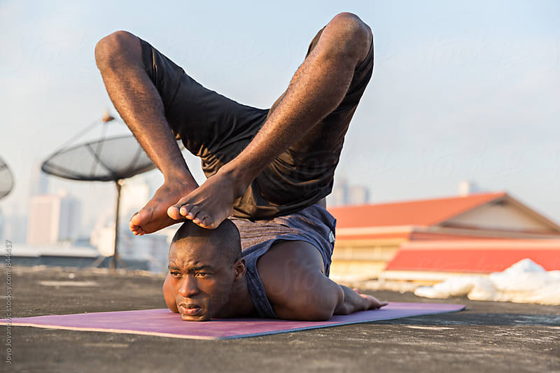 Young man in an advanced yoga practice on a city rooftop  by Jovo Jovanovic for Stocksy United