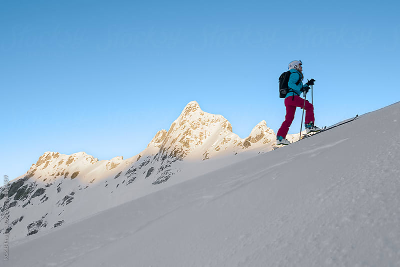 Woman going uphill on skis by RG&B Images for Stocksy United