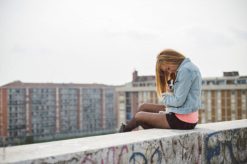 Young woman with her puppy on the wall above the city by GIC for Stocksy United