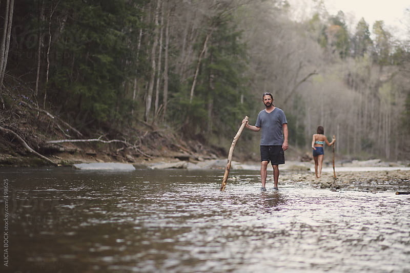 Man Walking In A River On A Family Hike by ALICIA BOCK for Stocksy United