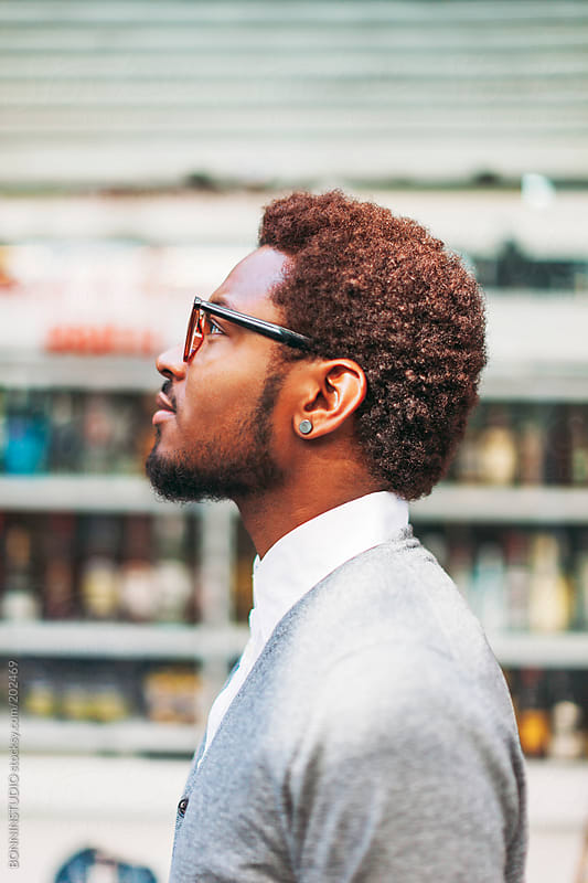 Side view of black man on the street in front a liquor store.  by BONNINSTUDIO for Stocksy United